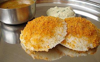 Kobbari podi sprinkled over steamed rice cakes (Idlis) with a dash of ghee
